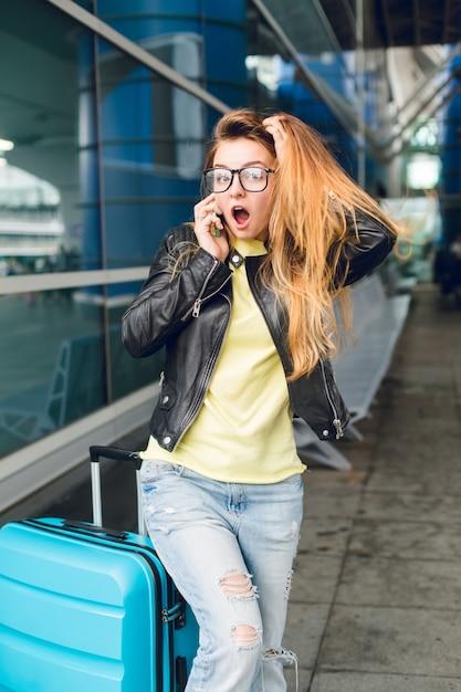 空港の外のスーツケースの近くに立ってメガネで長い髪のかわいい女の子の水平方向の肖像画。彼女は黄色いセーター、黒いジャケットとジーンズを着ています。彼女は面白そうだ。 無料写真