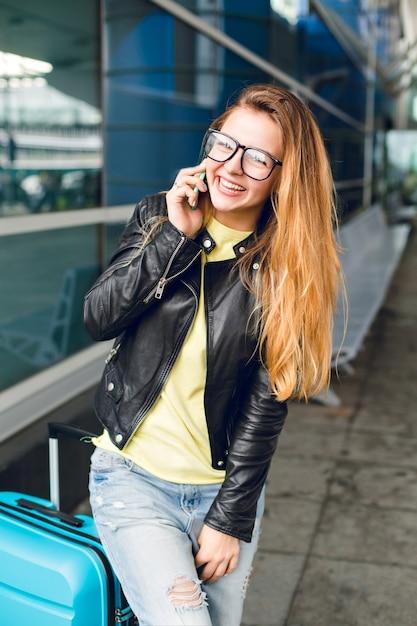 空港で外に立っている長い髪のかわいい女の子の水平方向の肖像画。彼女は黄色いセーター、黒いジャケットとジーンズを着ています。彼女は電話で話し、カメラに微笑んでいます。 無料写真