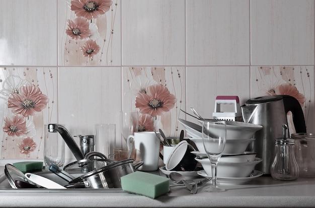 Огромная куча немытой посуды в кухонной раковине и на столешнице Premium Фотографии