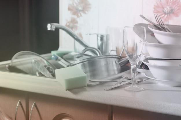 Огромная куча немытой посуды в кухонной раковине Premium Фотографии