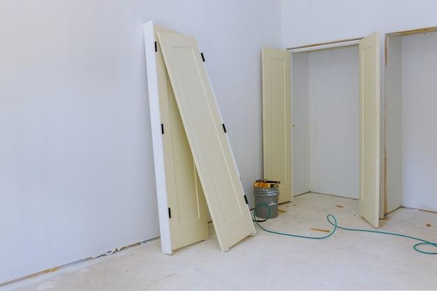 Установка межкомнатных деревянных дверей в ожидании укладчика нового дома Premium Фотографии