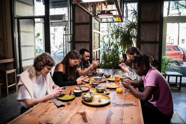 カフェで食べ物を共有し、無料のwifiを使用している学生の国際的なグループ Premium写真