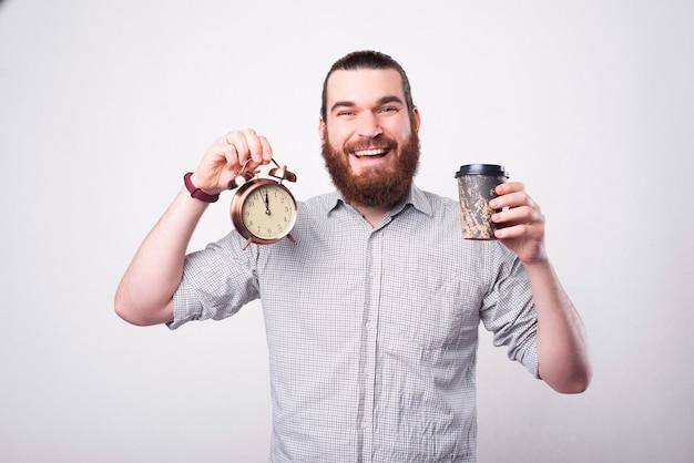 うれしそうなあごひげを生やした男が彼のコーヒーと小さな時計を持って、笑顔が白い壁の近くのカメラを見ています Premium写真