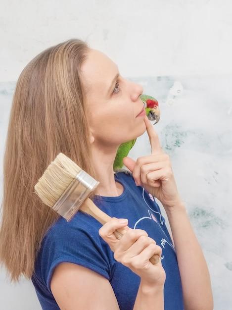 緑のオウムを持つ女性は家の修理を夢見ています。 Premium写真
