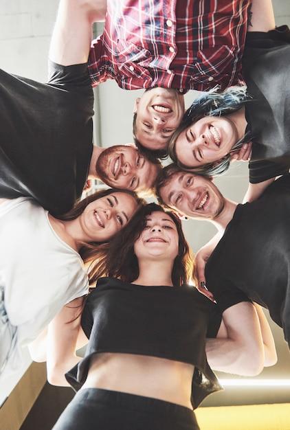 Большая группа улыбающихся друзей обнимаются вместе. Бесплатные Фотографии