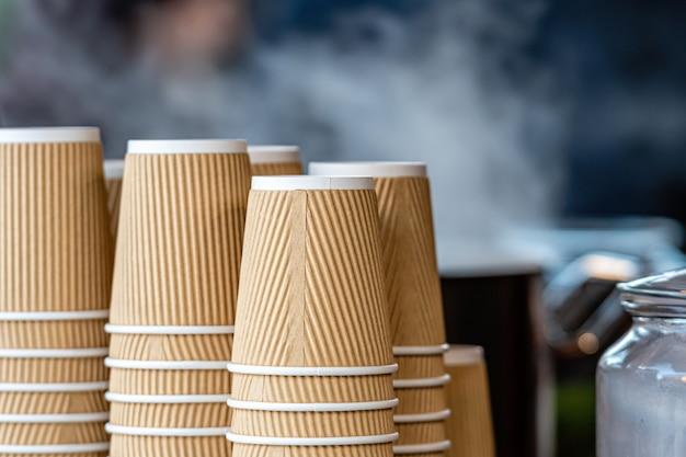 Большая стопка бумажных стаканчиков рядом с кофеваркой в уличном кафе на рождественской ярмарке Premium Фотографии