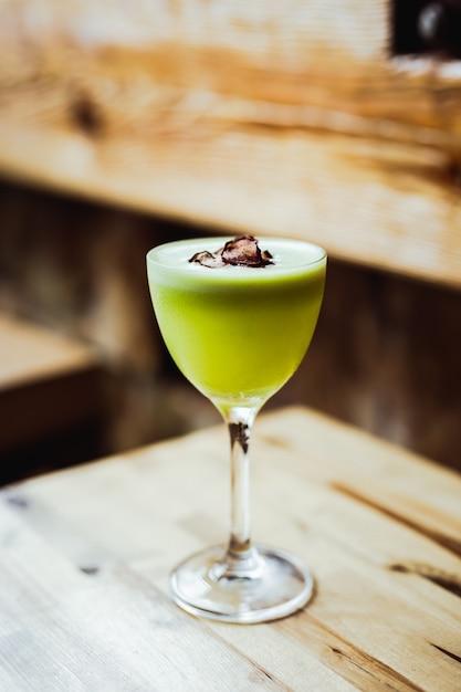 Светло-зеленый кислый коктейль из текилы в стакане nick and nora с гарниром из чипсов из редиса на деревянном столе Premium Фотографии