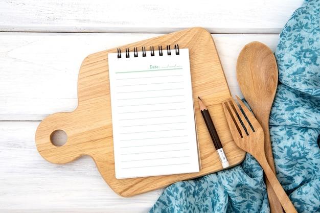 木製のフォークとカッティングボードとテーブルクロスを切り刻んで並べ替えられた本のメモ帳の紙と Premium写真