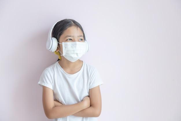 医療用防護マスクとイヤホンを身に着けている小さなアジアの女の子 Premium写真