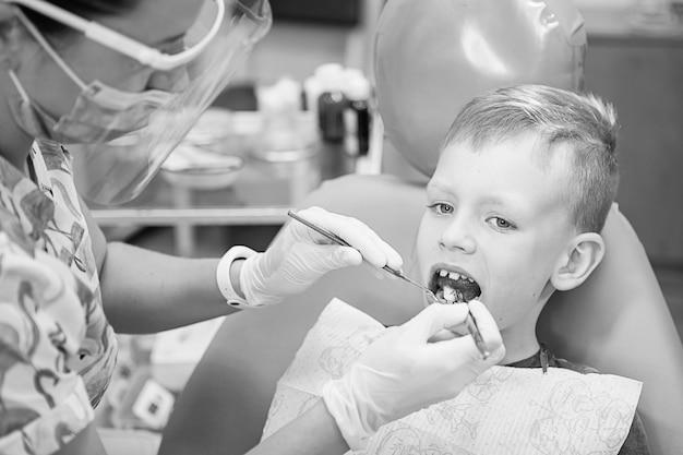 치과 클리닉에서 치과 의사의 리셉션에서 어린 소년. 어린이 치과, 소아 치과. Blac 및 흰색 복고 스타일 사진. 구강 건강 및 위생 프리미엄 사진