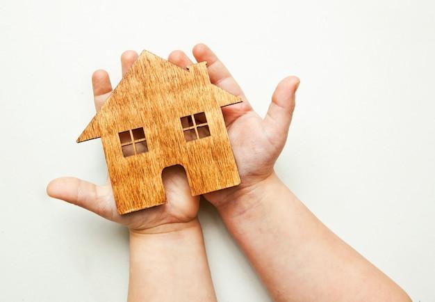 小さな子供は彼の手で木製の平らな家を保持しています。 Premium写真