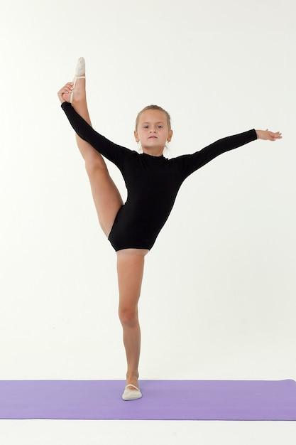 Маленькая девочка в черном трико гимнастки выполняет упражнение Premium Фотографии