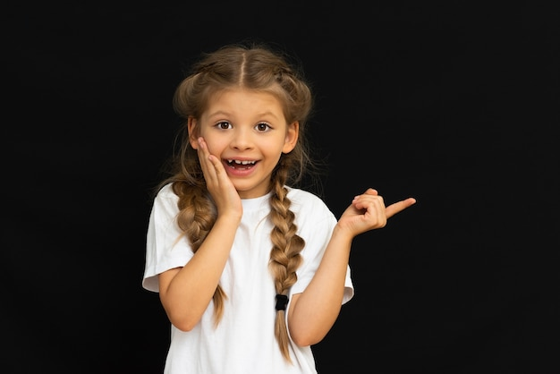 Маленькая девочка в белой футболке показывает удивление. Premium Фотографии