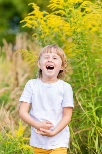 Маленькая девочка в белой футболке стоит среди желтых осенних цветов в поле и улыбается. Premium Фотографии