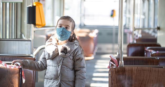 パンデミックコロナウイルスの最中、空の公共交通機関にいる少女。 Premium写真