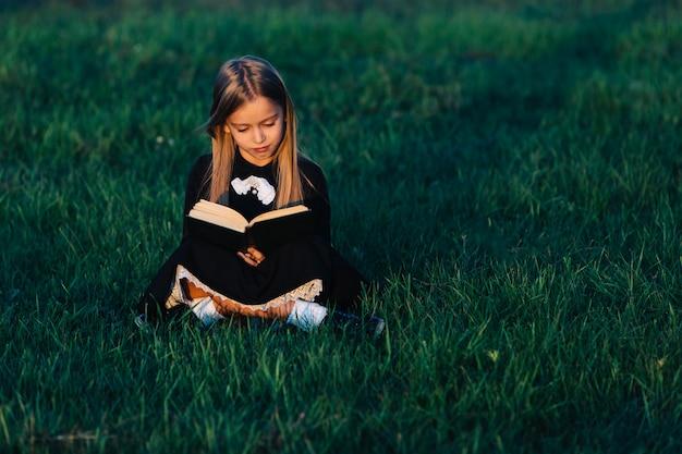 黒の少女が草の上に座って、夕日に照らして緑の本を持っています。子供は自然の中で屋外で読書します。 Premium写真