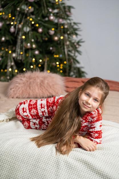 Маленькая девочка в пижаме рано утром нашла под елкой подарок от санты. рождественская волшебная сказка. счастливое детство. Premium Фотографии