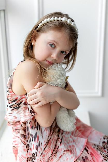 Маленькая девочка сидит у окна с игрушкой на руках Premium Фотографии