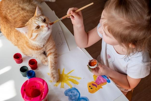 小さな女の子が太陽を描き、母親が水彩絵の具でテーブルの横に生姜猫が横たわっています。 Premium写真