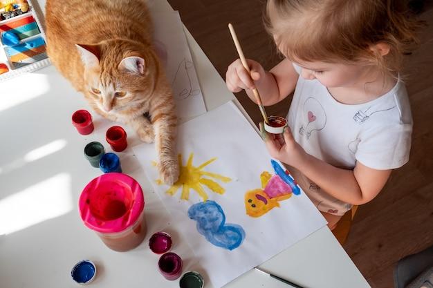 小さな女の子が太陽と母親を水彩で描く Premium写真