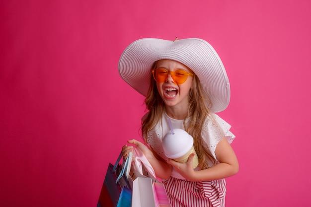 쇼핑백을 많이 들고 선글라스와 모자를 쓰고 웃는 어린 소녀 프리미엄 사진