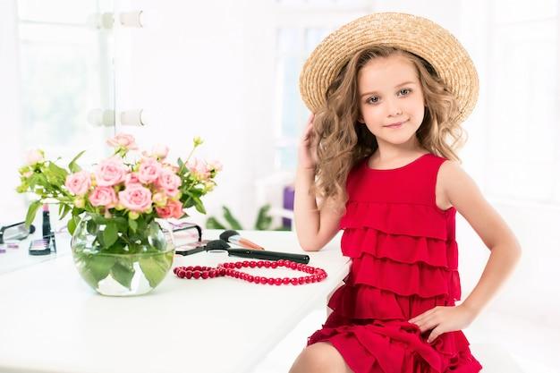 赤いドレスと化粧品を持つ少女。 無料写真