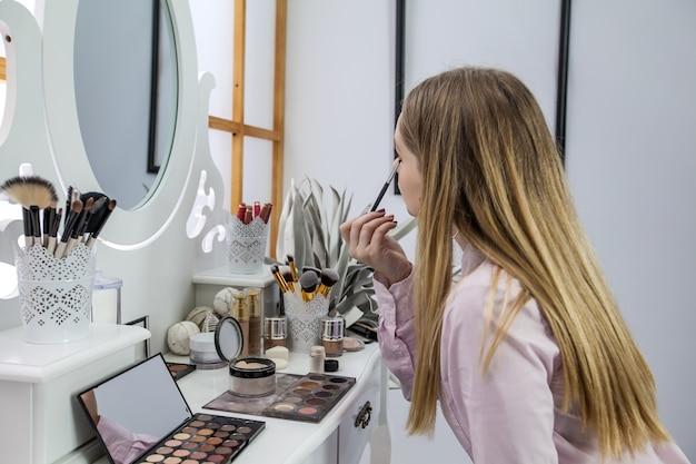 A自分を鏡に映し、化粧をしている 無料写真