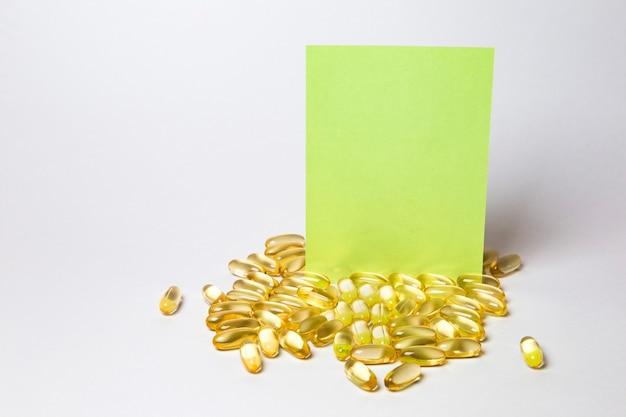 テキストのメモにコピースペースと白い背景の上の多くのカプセルの丸薬 Premium写真