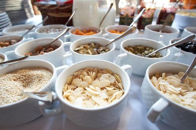 Много полезных закусок на завтрак из орехов, сухофруктов, меда и овса в открытом буфете Premium Фотографии