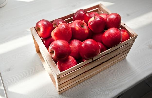 台所の木製のテーブルの上の木箱でジューシーな赤いリンゴがたくさん Premium写真