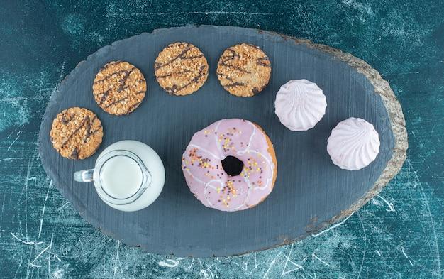 어두운 보드에 우유와 함께 많은 달콤한 과자. 고품질 사진 무료 사진