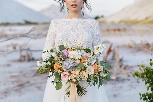 Роскошный букет экзотических цветов в руке молодой женщины в кружевном платье Premium Фотографии