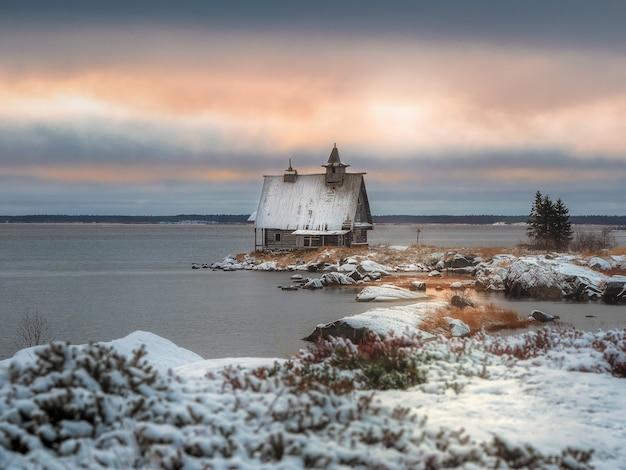 포메라니안 마을의 환상적인 일몰. 러시아 마을 Rabocheostrovsk의 해안에 정통 집 눈 덮인 겨울 풍경. 프리미엄 사진
