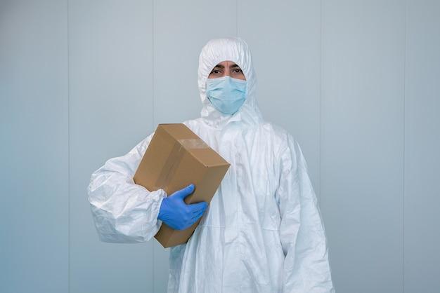 Медсестра в защитном костюме сиз показывает ящик в больнице. медицинский работник получает медицинские принадлежности для ухода за пациентами с коронавирусом или covid 19 Premium Фотографии