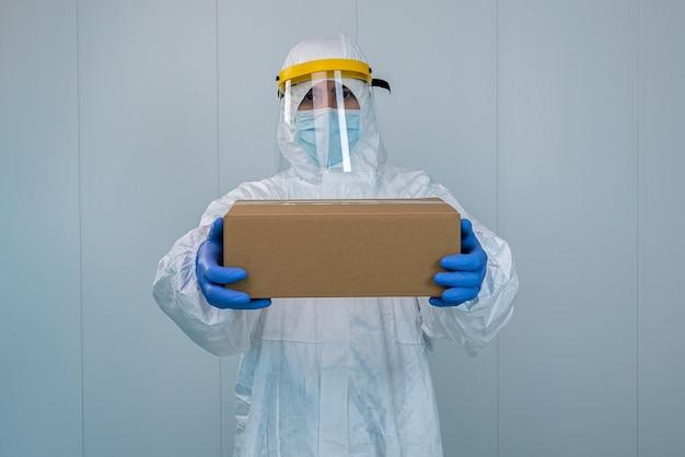 Медсестра в костюме защитного снаряжения и защитной маске показывает ящик в больнице. медицинский работник получает медицинские принадлежности для ухода за пациентами с коронавирусом или covid 19. Premium Фотографии