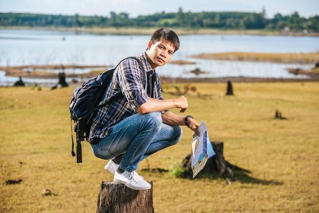 地図を運んで木の切り株に座っているバックパックを持つ男性旅行者。 無料写真