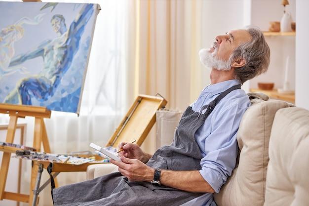 한 남자 예술가가 뮤즈가 걸작을 만들기를 기다리고 있으며, 생각에 빠져 예술 스튜디오에서 소파에 앉아 생각하고 있습니다. 프리미엄 사진