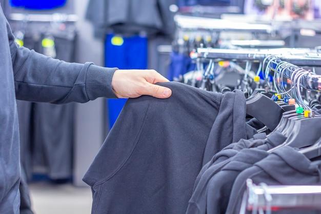 スポーツ店でスウェットシャツやパーカーを選択する男 Premium写真