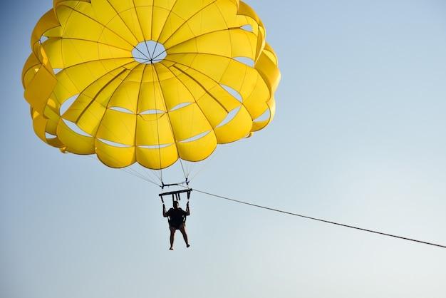 夕暮れ時に海をパラシュートで飛ぶ男 Premium写真