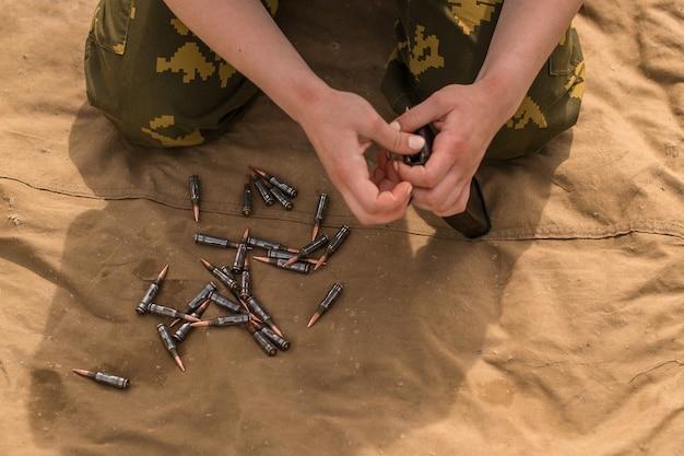 Мужчина из армии управляет автоматом калашникова с 7, 62 патронами. солдат сидит на ткани и заряжает оружие. Premium Фотографии