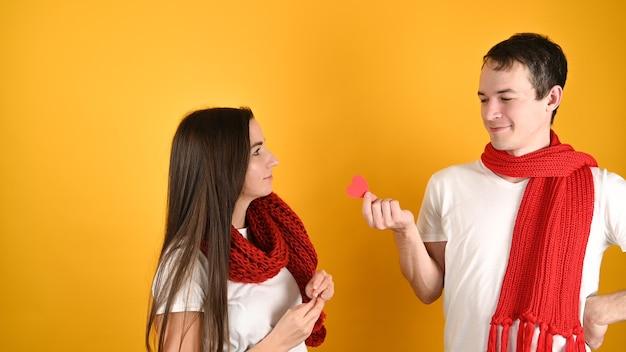 Мужчина дарит сердце женщине на желтом Premium Фотографии