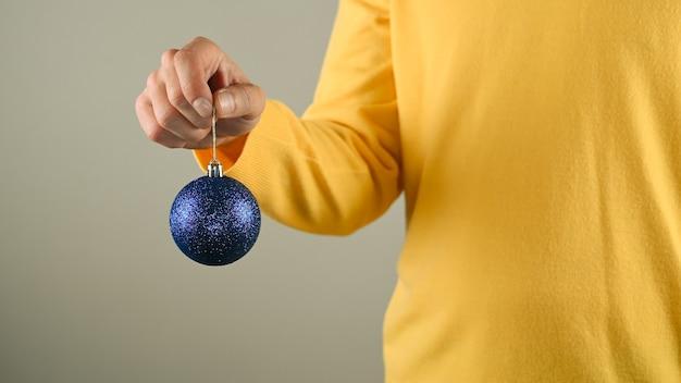 Мужчина держит в руке синий елочный шар. Premium Фотографии