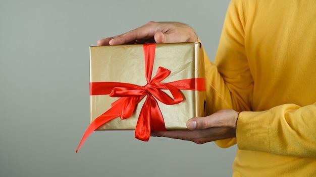 Мужчина держит подарочную коробку с красным бантом. Premium Фотографии