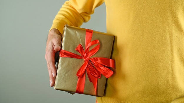 Мужчина держит подарочную коробку. Premium Фотографии