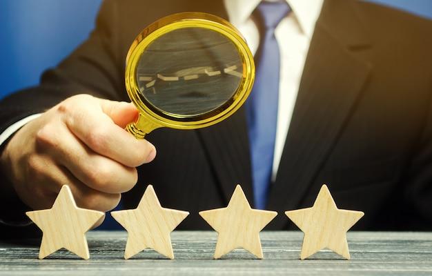 Мужчина держит увеличительное стекло над четырьмя звездами. Premium Фотографии