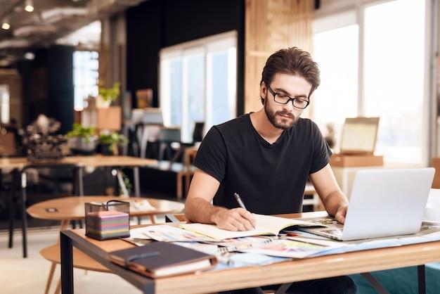 검은 색 티셔츠를 입은 남자가 테이블에 앉아서 작동합니다. 프리미엄 사진