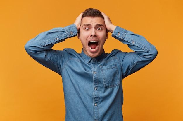 Мужчина в панике схватился за голову, громко закричал, поражение произошло поражение провал, одет в джинсовую рубашку Бесплатные Фотографии
