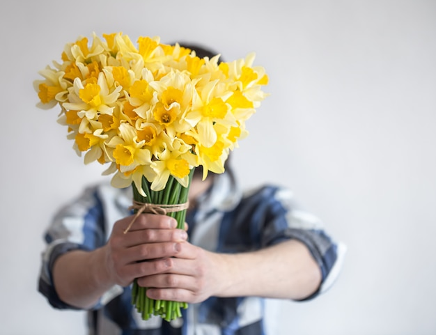 シャツを着た男性が花束で顔を覆っている 無料写真