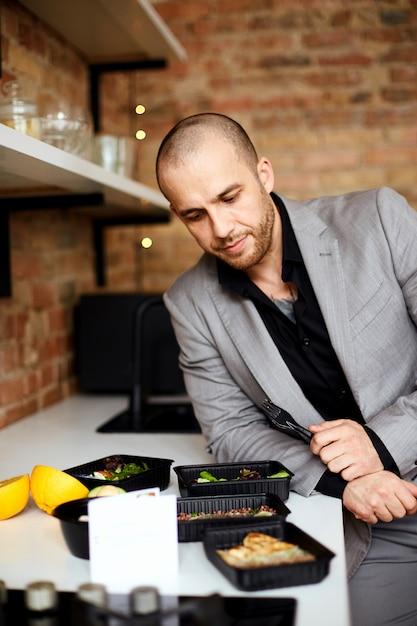 양복 입은 남자가 점심을 먹고있다. 음식 배달 프리미엄 사진