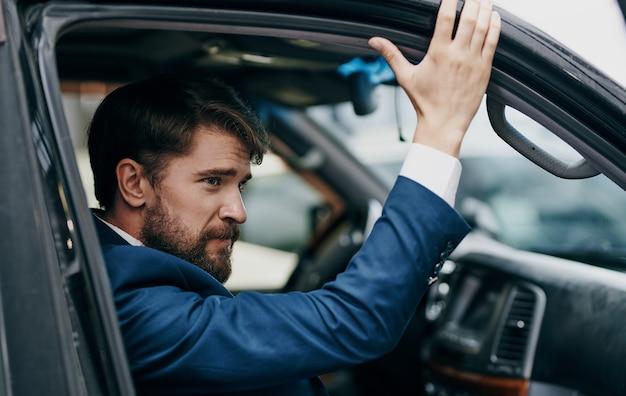 スーツを着た男性が窓の外を眺める車に乗って楽しいライフスタイル。 Premium写真
